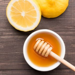 Bowl of sweet honey and lemons on wooden table.