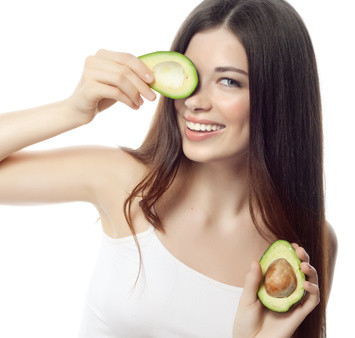 portrait of attractive caucasian smiling woman isolated on white studio shot with avocado