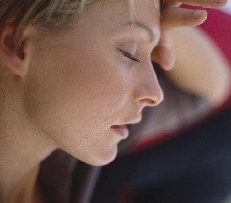 Side profile of a young woman holding her forehead