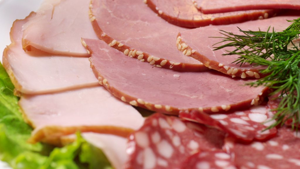 Cutting bacon, sausage and cured meat on a celebratory table ; Shutterstock ID 179482388; PO: today-food