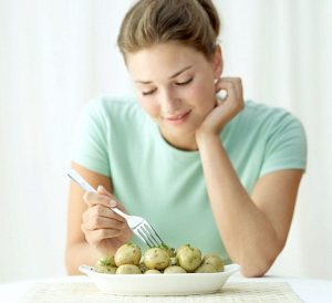 Caption Young woman holding a fork in a dish of potatoes By Stockbyte Releases Model: YES / Property: NO